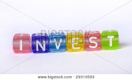Text Invest On Colorful Wooden Cubes