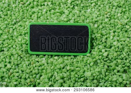 Hand Holding Noticeboard  On Green Color Sand