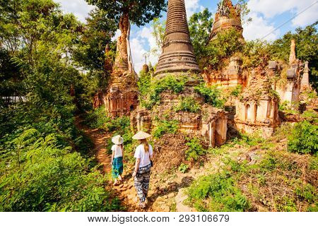 Back view of family mother and daughter visiting hundrets of centuries old stupas in Indein near lake Inle in Myanmar