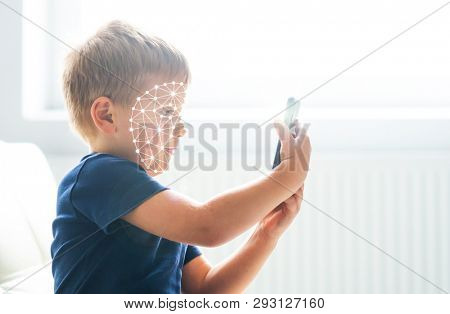 Kid using face id recognition. Boy with a smartphone gadget. Digital native children concept.