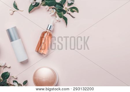 Pink Natural Cosmetics: Oil, Serum, Cream, Mask On Background With Flowers. Flat Lay, Minimalism.