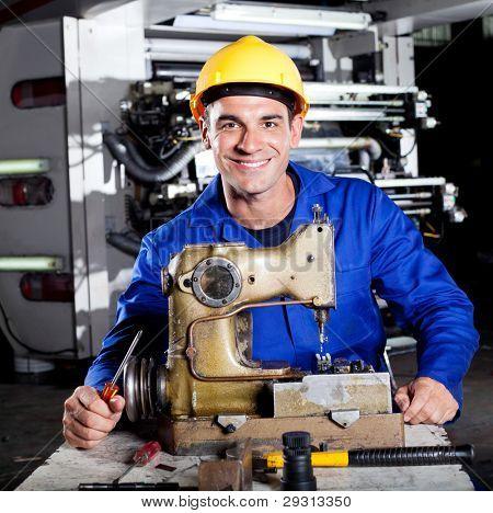 happy mechanic repairing industrial sewing machine in factory