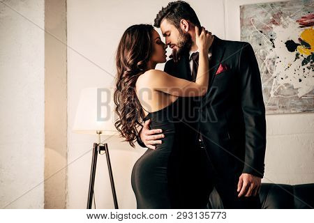 Attractive Woman In Black Dress Hugging With Passionate Man In Suit