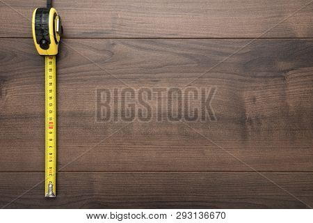 Tape Measure Over Wooden Background. Photo Of Tape Measure With Copy Space. Top View Of Yellow Tape