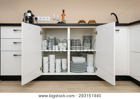 Dishware storage cabinet with open doors, white plates, bowls cups and other china crockery inside, front view poster