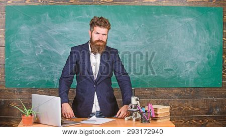 Teacher interesting interlocutor as authority. Teacher charismatic hipster stand near table classroom chalkboard background. Talking to students or pupils. Teacher bearded man tell scary story poster