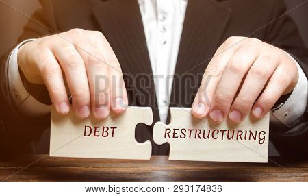 Businessman Collects Wooden Blocks With The Word Debt Restructuring. Debts Relief. Changing Loan Rep