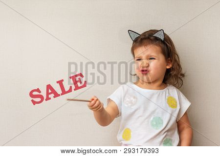A Little Girl With Pouting Lips And Provoking Emotion Points To The Words Sale, Close-up,