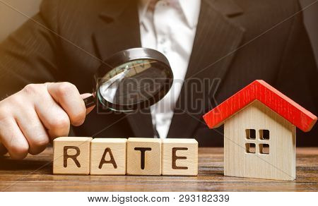Wooden Blocks With The Word Rate, House And A Magnifying Glass In The Hand Of A Man. The Concept Of