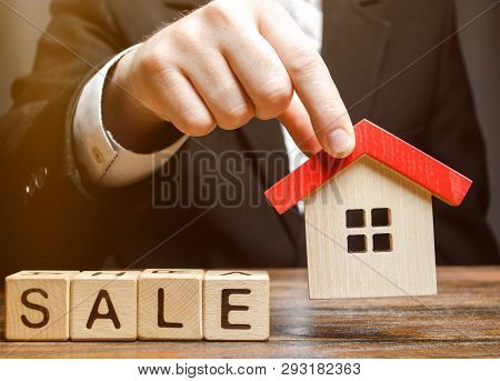 Wooden Blocks With The Word Sale And Miniature House In The Hands Of A Real Estate Agent. Real Estat