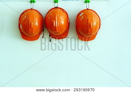 Orange Safety Hat Hanging On Wall At The Factory