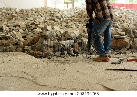 The  Worker Using Dismantling Machine Hitting Into The Concrete  Ground