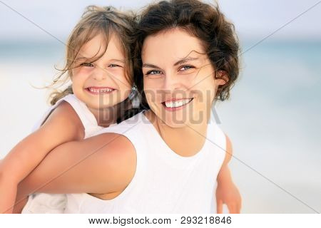 Portrait of happy mother and little daughter on sunny beach on Maldives at summer vacation