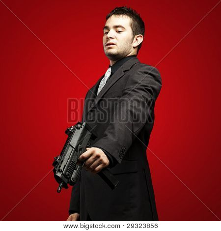 mafia man aiming down with gun against a red background