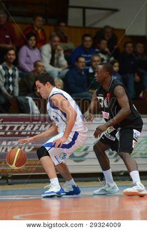 KAPOSVAR, HUNGARY - JANUARY 21: Kornel Kiss (L) in action at a Hungarian National Championship basketball game with Kaposvar (white) vs. Szolnok (black) on January 21, 2012 in Kaposvar, Hungary.