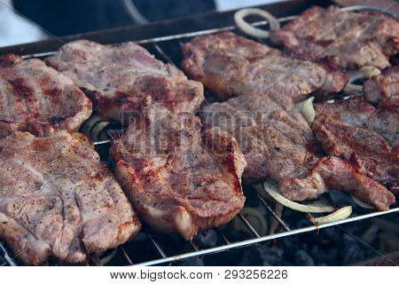Steak Grilling On Fire. Process Of Cooking Meat. Steak On Barbecue. Pieces Of Grilled Meat On Grill.