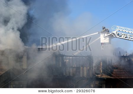 Firemen putting out a fire on a turntable ladder
