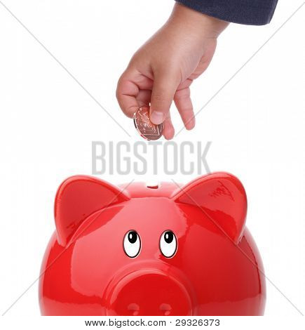 Baby boy putting coin into a piggy bank