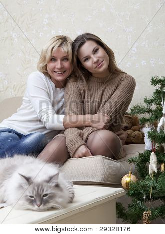 Portrait of mother and daughter with a cat poster