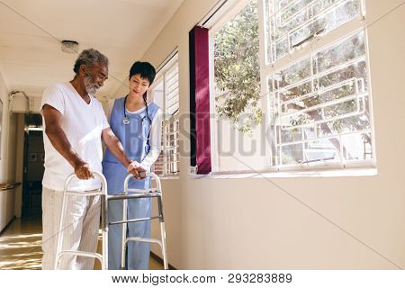 Front view of Asian female nurse helping senior Caucasian male patient to walk with walker in corridor at retirement home