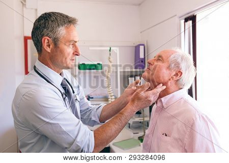 Side view of confident matured Caucasian male doctor checking senior Caucasian man in clinic at retirement home. Doctor touching patients neck.