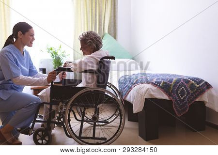 Side view of mixed race nurse talking with senior mixed race female patient at nursing home. Senior female sits in a wheelchair.
