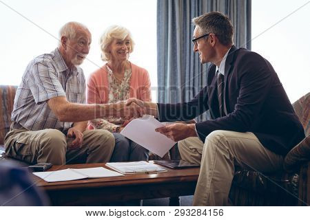 Front view of matured Caucasian male physician interacting with senior Caucasian couple at retirement home. Both men shaking hands