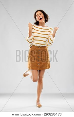 success and people concept - happy smiling young woman in striped pullover, short skirt and ballet flat shoes celebrating triumph over grey background