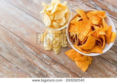 fast food, junk-food, cuisine and eating concept - close up of crunchy potato and corn crisps or nachos in bowls on wooden table