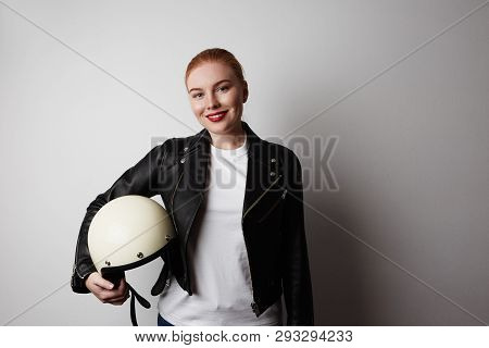 Handsome Woman Wearing Black Leather Jacket And White Moto Helmet Over Background. Fashion, Glamour