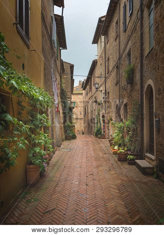 Beautiful and colorful streets of the small and historic Tuscan village Pienza, Italy poster