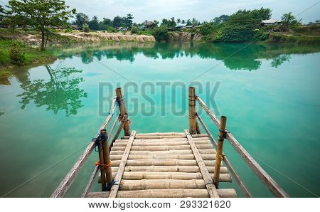 Wooden Pier On Green Blue Lagoon, Tropical Paradise. Traditional Bamboo Pier Or Jetty On Lakeside. C