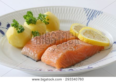 Salmon Fillet With Potatoes, Lemon Slices And Parsley Served On A Plate. Close Up Stock Photo.