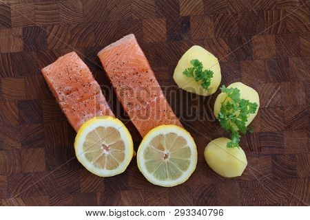 Salmon Fillet With Potatoes, Lemon Slices And Parsley Served On A Wooden Board. Top View Close Up St