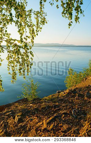 Summer landscape - sunset view of summer lake framed by birch trees. Sunset over the Irtyash lake in Southern Urals, Russia, colorful summer water landscape. Summer sunset nature