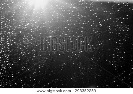 Rain Drops And Defocused Sky Background In Black And White. Seasonal Background Texture For Design.