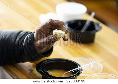 Elderly Man Eats Warm Soup With Bread In A Kitchen With Free Food For Poor And Homeless People.