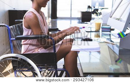 Mid section of young disabled mixed-race businesswoman working on computer at desk in the modern office