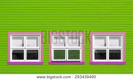 Pink and white windows on a lime green wooden wall. Minimalism style of the houses of Iles de la Magdalen, Canada, in bright colours with space for text.