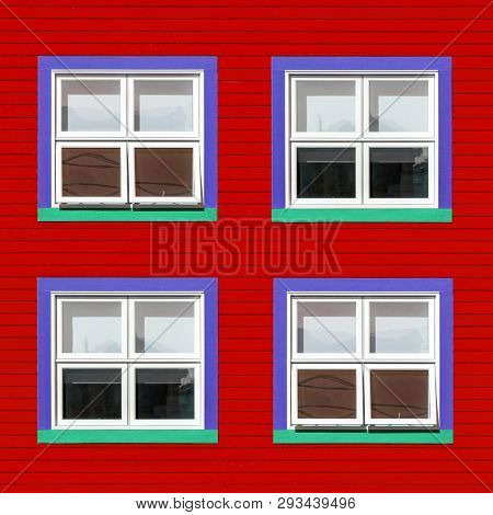 Purple, green and white windows on a red wooden wall. Minimalism style of the houses of Iles de la Magdalen, Canada, in bright colours with space for text.