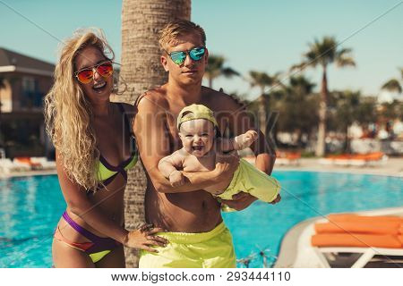 Beautiful Family With A Child Relaxing At The Blue Pool.