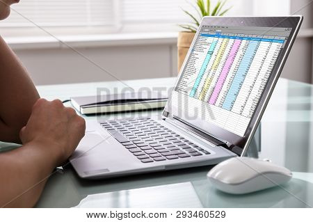 Businessperson Examining Reports On Laptop