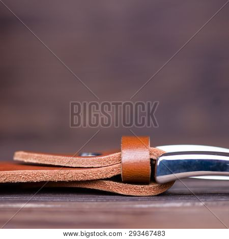 Ginger Color Handmade Belt Buckle Lies On Textured Wooden Background Closeup. Side View. Stock Photo
