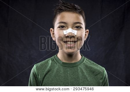 Happy And Athletic Boy. A Close Up Portraiture Of A Confident Athletic Boy Who Has Tape On His Nose