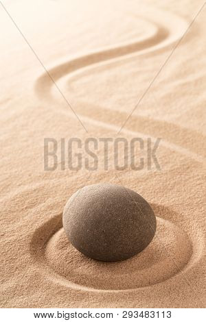 Japanese zen meditation stone garden with round rock in raked sand.