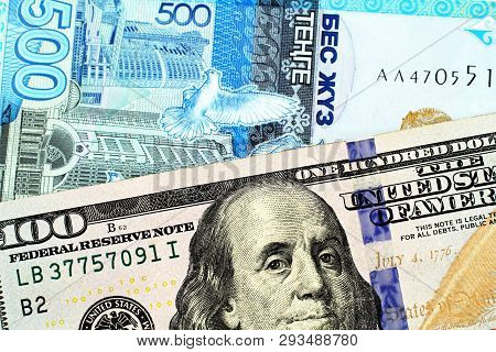 An American One Hundred Dollar Bill Close Up With A Five Hundred Tenge Bank Note From Kazakhstan In