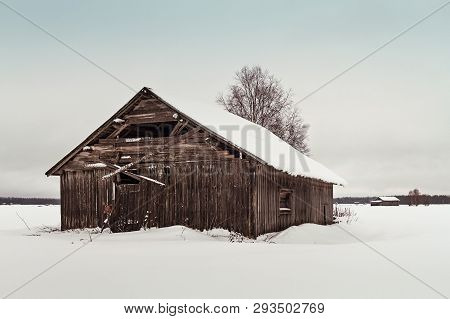 An Old Abandoned Barn House Stands On The Snowy Fields Of The Rural Finland. The Weather Is Cold And
