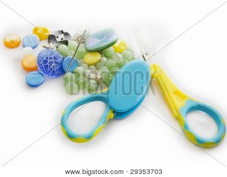 Closeup of buttons, needle and scissors