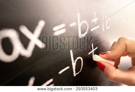 Math Teacher Writing Function, Equation Or Calculation On Blackboard In School Classroom. Student Ca