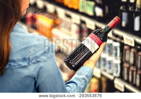Woman Reading The Label Of Red Wine Bottle In Liquor Store Or Alcohol Section Of Supermarket. Shelf